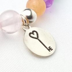 Pulsera abrecaminos medalla llave corazón en plata de ley y minerales de cuarzo rosa.